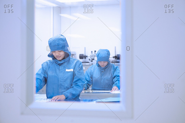 Female workers inspecting flex circuits in flexible electronics factory clean room