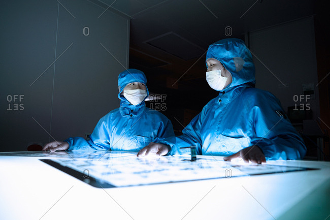 Female workers discussing flex circuit in flexible electronics factory clean room
