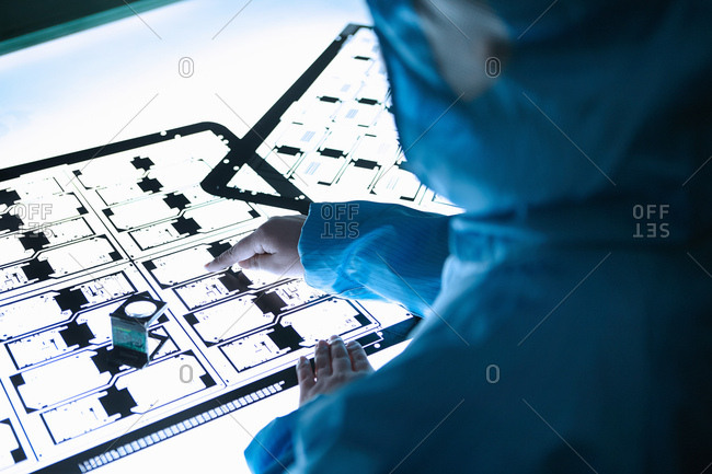 Female worker inspecting flex circuit on lightbox in flexible electronics factory clean room