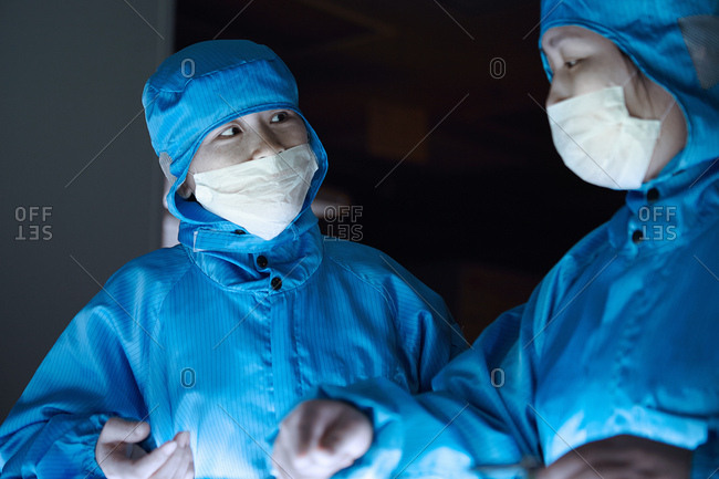 Female workers wearing protective clothing in flexible electronics factory clean room