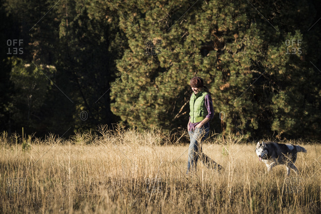 Mid adult woman walking dog in tall grass looking down smiling, Missoula, Montana, USA