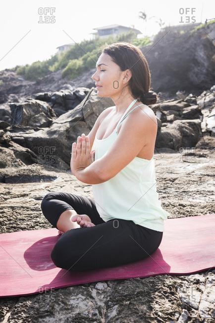 Woman practicing yoga lotus position on beach