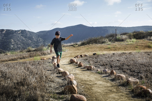 Boy stepping across row of footpath stones, Thousand Oaks, California USA