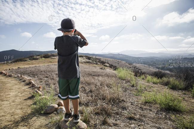 Rear view of boy looking through binoculars from footpath stone, Thousand Oaks, California USA