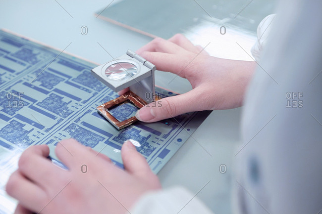 Hands of female worker inspecting flex circuit in flexible electronics factory