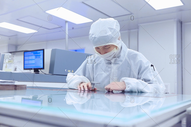 Female worker inspecting product in flexible electronics factory clean room