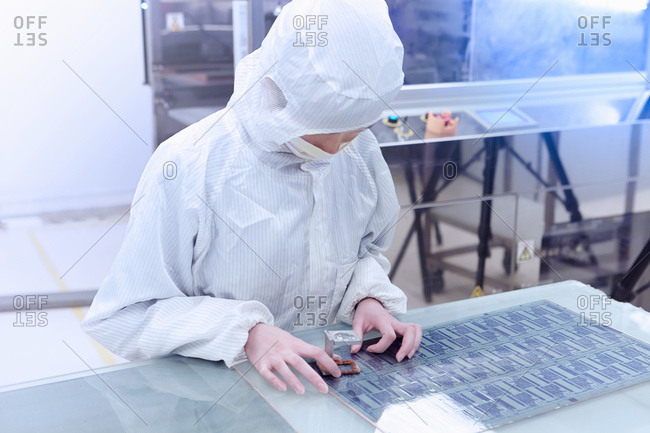 Female worker using loupe in flexible electronics factory clean room
