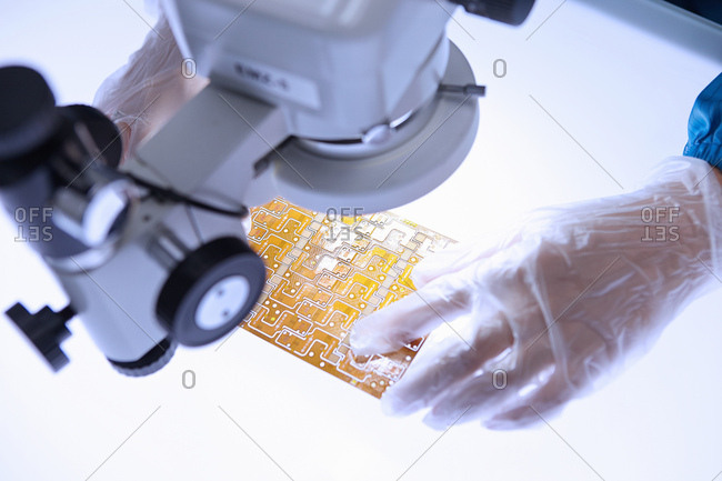 Hand of female worker using microscope to examine flex circuit in flexible electronics factory clean room
