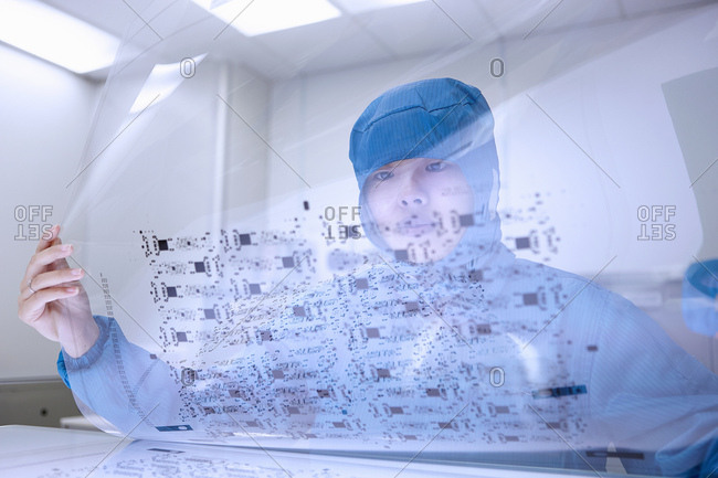 Female worker holding flex circuit in flexible electronics factory clean room