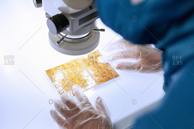 Over the shoulder view of female worker using microscope to examine flex circuit in flexible electronics factory clean room