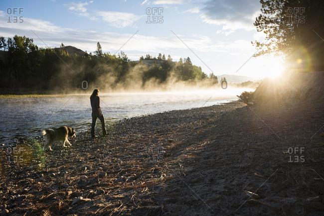 Woman walking dog on bank of Bitterroot River, Missoula, Montana, USA
