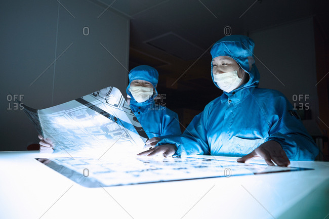 Female workers inspecting flex circuit on lightbox in flexible electronics factory clean room