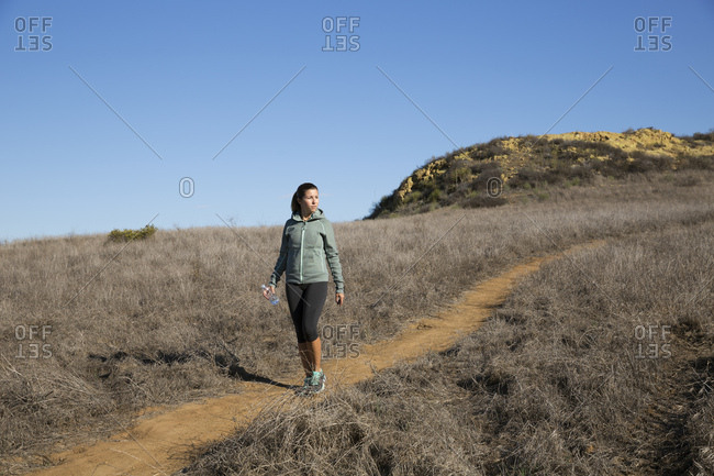 Female runner moving down hill path