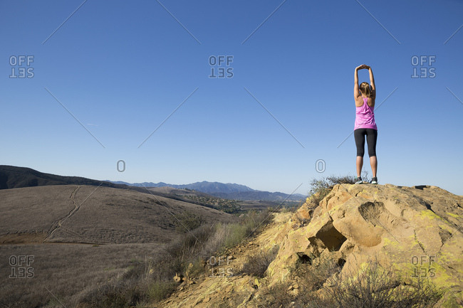 Rear view of woman practicing yoga pose on top of hill, Thousand Oaks, California, USA
