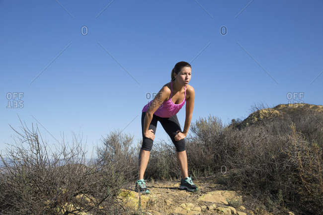 Exhausted female runner on top of hill