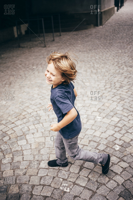 High angle side view of boy running on cobblestone smiling, Bludenz, Vorarlberg, Austria