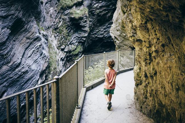 Rear view of boy walking with hands behind back on elevated walkway winding through mountains, Hinterrhein, Switzerland