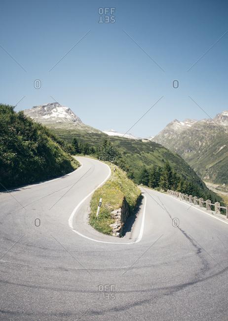 Open road winding down mountainside, Hinterrhein, Switzerland