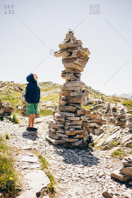 Boy standing by stack of rocks looking up, Hinterrhein, Switzerland