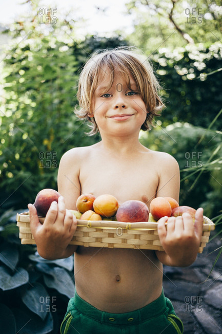 Boy holding basket of fruit looking at camera smiling, Bludenz, Vorarlberg, Austria