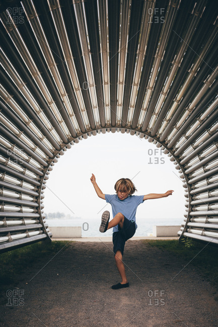 Boy in corrugated tunnel, arm open leg raised