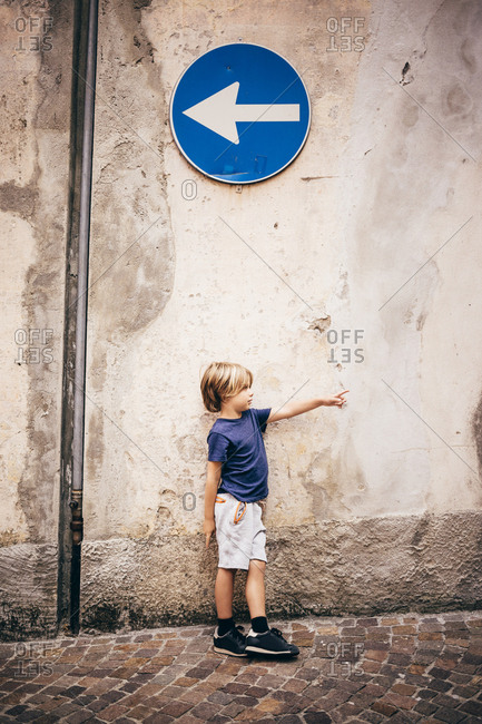Boy leaning against wall underneath direction sign pointing