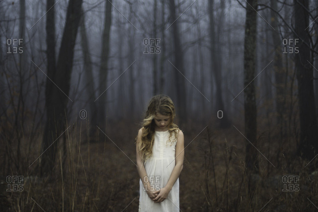 Portrait of long blond haired girl with head bowed in misty forest