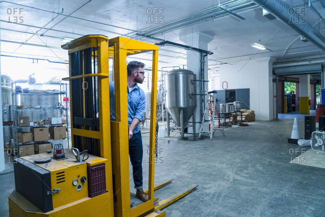 Young man in brewery driving forklift truck, looking away