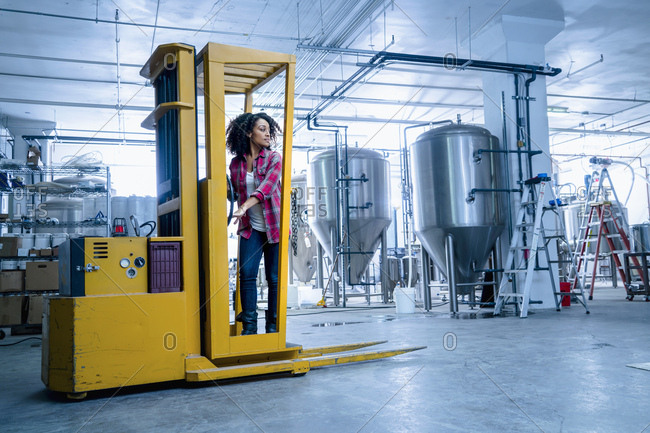 Mid adult woman in brewery driving forklift truck looking away