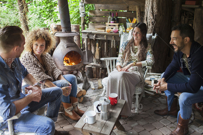 Four adult friends drinking coffee in open cabin with wood stove