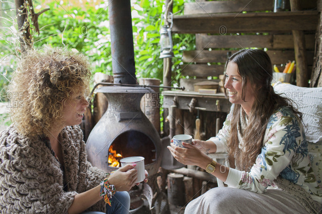 Two female friends drinking coffee in open cabin with wood stove