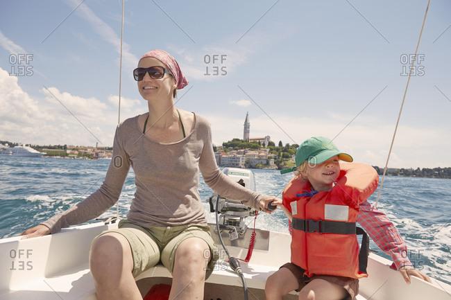Mature woman with son steering motor boat, Rovinj, Istria Peninsula, Croatia
