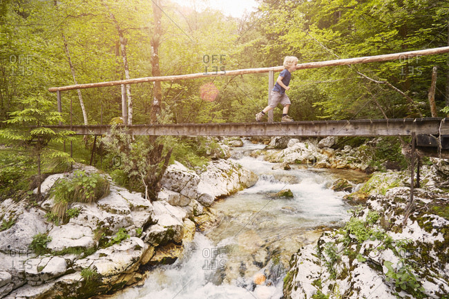 Boy running on wooden footbridge, Bovec, Soca, Slovenia