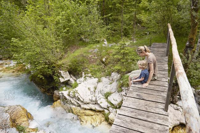 Mature woman with son sitting on wooden footbridge, Bovec, Soca, Slovenia