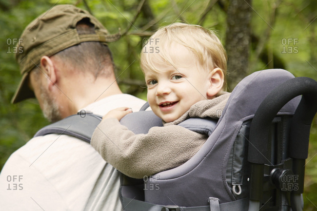 Portrait of male toddler in fathers hiking baby carrier, Bovec, Soca, Slovenia
