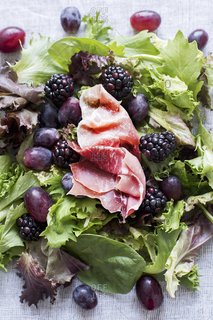 Green salad with grapes, berries and prosciutto