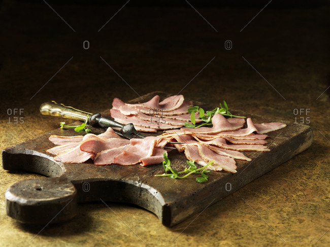 Rustic still life with sliced duck (cooked three ways) on chopping board