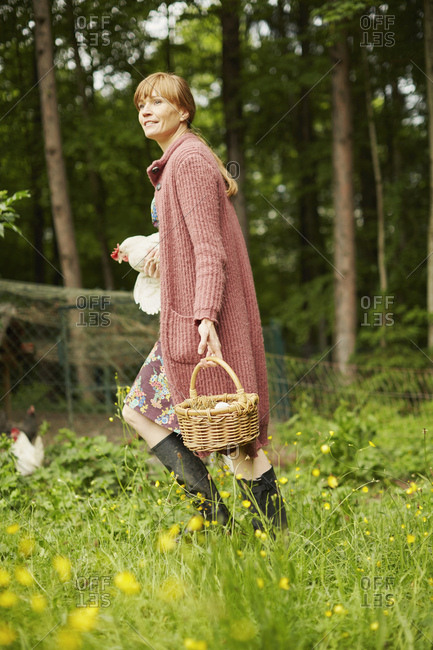 Woman carrying hen and egg basket
