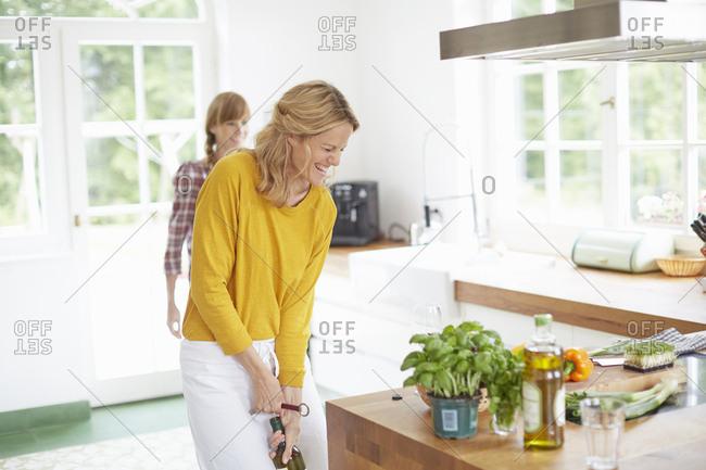 Woman opening wine bottle in kitchen