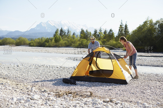 Couple erecting yellow tent near water, Wallgau, Bavaria, Germany