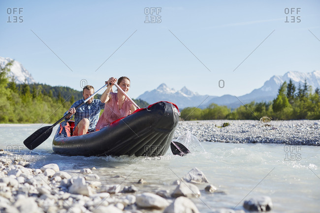 Couple using paddles to steer dinghy on water, Wallgau, Bavaria, germany