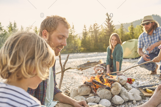 Family sitting around campfire cooking fish attached to branch
