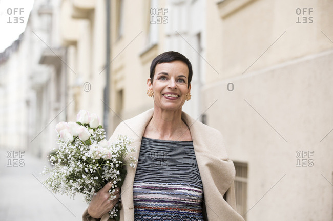 Woman with flowers walking on street