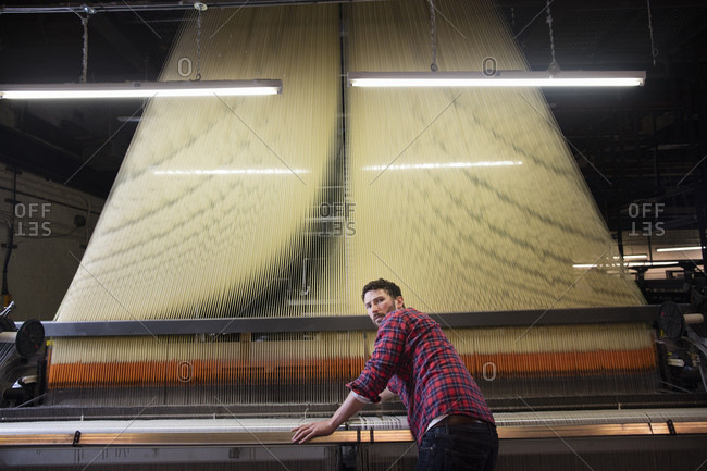 Overhead portrait of young male weaver at old weaving machine in textile mill