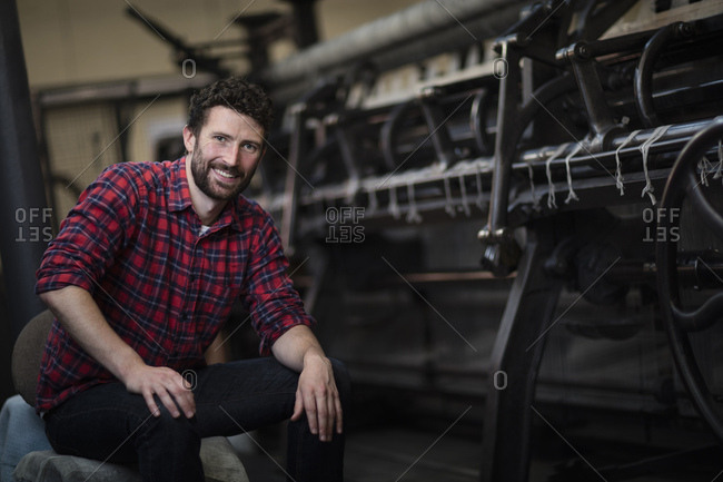 Portrait of young male weaver at old weaving machine in textile mill