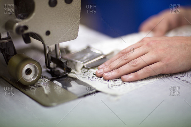 Hands of male textile designer using sewing machine in old textile mill