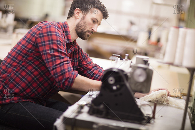Male weaver using sewing machine in old textile mill