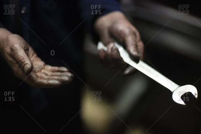 Oily hands of male weaver fixing old weaving machine in textile mill