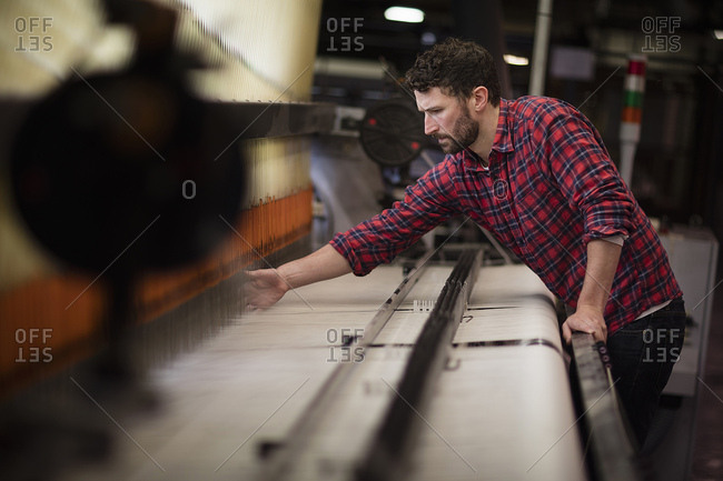 Young male weaver using old weaving machine in textile mill