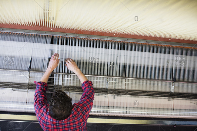 Overhead view of young male weaver adjusting threads on old weaving machine in textile mill